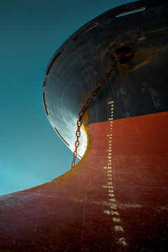 Ship's bow with red waterline against the blue sky. World shipping freight concept
