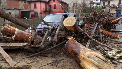 A van and debris are seen piled up next to a bridge in stream after flash floods in Castelletto D'Orba