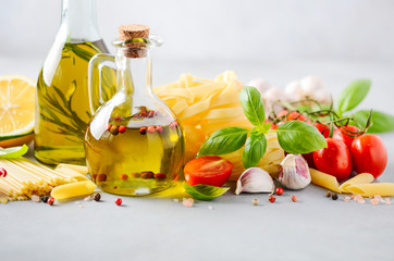 Italian food ingredients – pasta, tomatoes, basil and olive oil on gray concrete background.