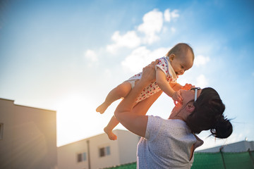 An emotional picture of 1 year old baby and her mother holding her up in the air against blue sky and bright sun