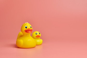 Two yellow rubber ducks toys, copy space. Cute funny bath toys, minimal kidult concept. Pink background.