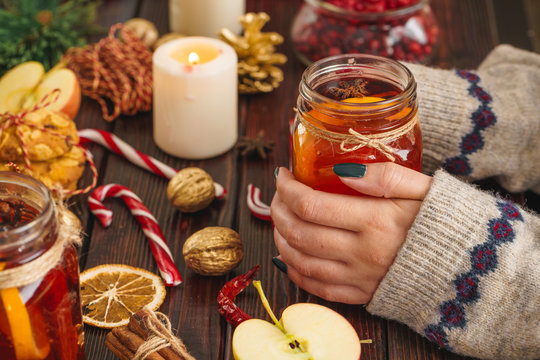 Cup of mulled wine in woman's hands on wooden table