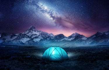 Wall Murals Camping Camping in the mountains under the stars. A tent pitched up and glowing under the milky way. Photo composite.