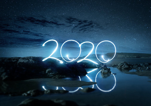 Night time 2020 light effect writing reflecting in water on a beach. Long exposure Landscape new year photo composite.