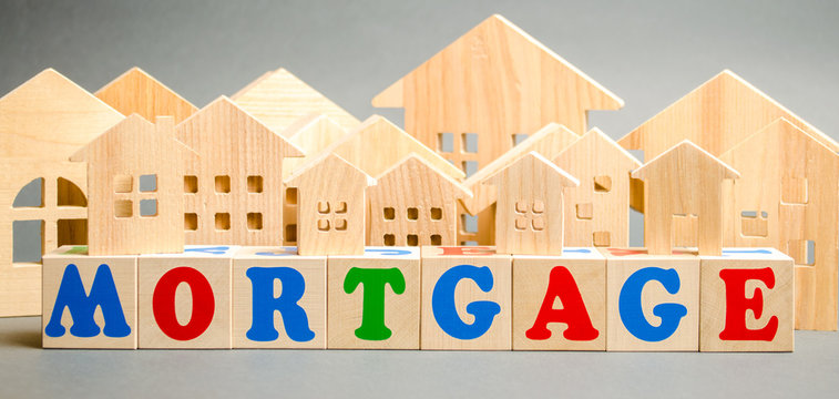 Wooden blocks with the word Mortgage and miniature houses. Loan form with a pledge. Buying real estate or housing on credit. Mortgage credit lending