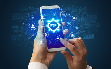 Female hand holding smartphone with FTP abbreviation, modern technology concept