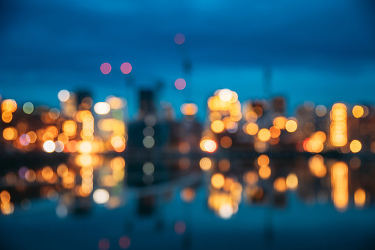 Oslo, Norway. Night Abstract Boke Bokeh Background Effect. Design Backdrop. Night View Embankment And Residential Multi-storey House In Gamle Oslo District. Residential Area Reflected In Sea Waters