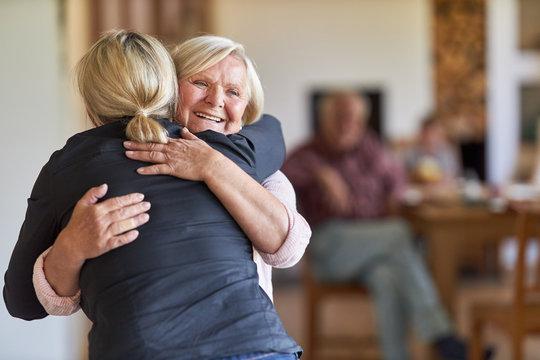 Tochter besucht glückliche Mutter im Altenheim
