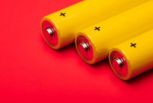 Yellow alkaline batteries on red background