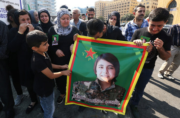 Kurds living in Lebanon react as they hold Rojinda Qendil's picture, during a protest against Turkey's military action in northeastern Syria