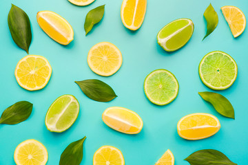 Ripe cut lemons and limes on color background