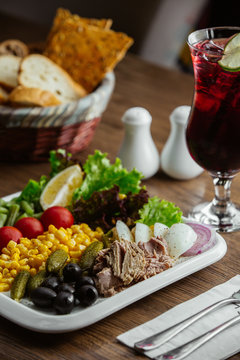 appitizers plate with olive, corn, boiled beef, lettuce, cornichon, tomato, lemon