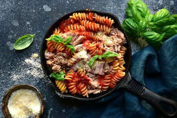 Fusilli pasta with tuna in tomato sauce. Top view with copy space.