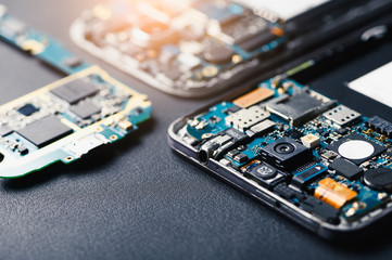 The inside of the smartphone's motherboard and sim card lay on the back table. the concept of computer hardware, mobile phone, electronic, repairing, upgrade and technology.