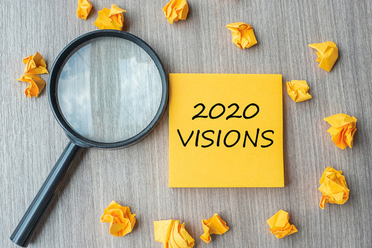 2020 VISIONS words on yellow note with crumbled paper and magnifying glass on wooden table background. New Year New Start, Idea, Strategy, and Goals concept