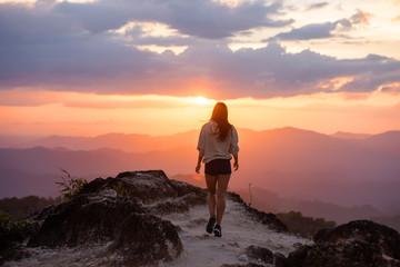 Slim beautiful girl walks mountains at sunset