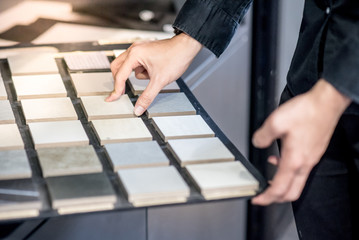 Male architect or interior designer hand choosing ceramic texture sample from swatch board in design studio. Floor and wall finishing material for architecture and construction industry.