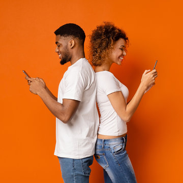 Side portrait of african couple standing back to back with mobile phones
