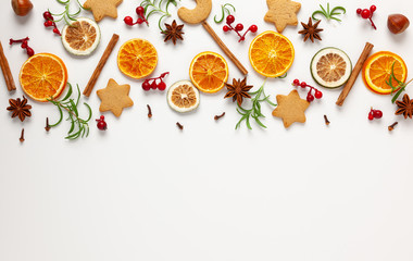 Christmas composition with cookies, dried oranges, cinnamon sticks and herbs on white background....
