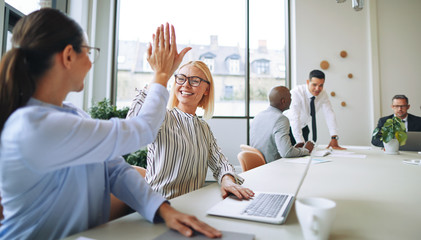 Two smiling young businesswomen high fiving together in a boardr