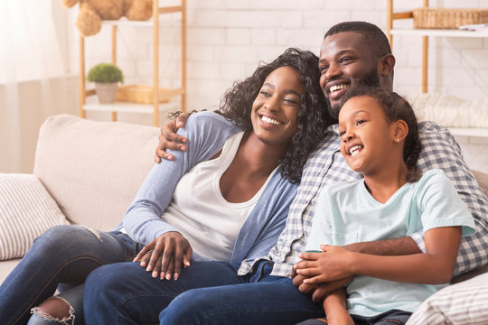 Father, mother and daughter watching tv together, relaxing at home
