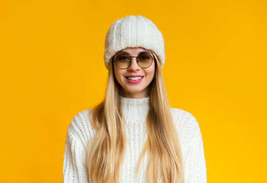 Cute cheerful winter girl in sunglasses smiling over yellow background