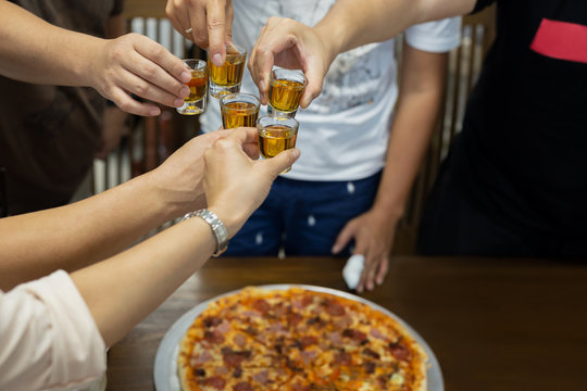 Friend with rum shots on party with pizza on table.
