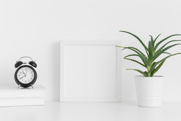 White square frame mockup with a aloe vera in a pot and workspace accessories on a white table.