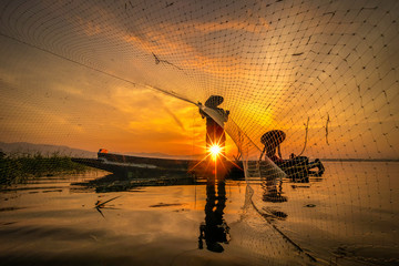 Fishermen Casting fishing early in the morning sunrise with wooden boats. Concept Fisherman's life style. Image is silhouette. .