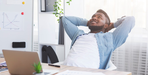 Satisfied office worker leaning on chair, relaxing after completed job