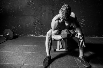 Young strong muscular sweaty fit man biceps muscle workout cross training with heavy dumbbell in the gym dark image with shadows real people black and white