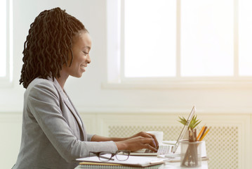 African American Woman Working On Laptop In Office, Side View