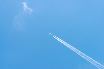 Airplane in a blue sky with clouds and condensation trails, Germany