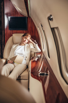 attractive businesswoman in suit sleeping with book in private plane
