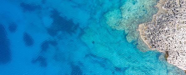 An aerial view of the beautiful Mediterranean sea, where you can se the rocky textured underwater corals and the clean turquoise water of blue lagoon Agia Napa