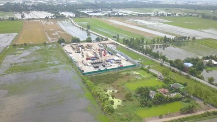 Wall Mural - Oil and gas a land rig, onshore drilling rig, in the middle of a rice field aerial view from a drone