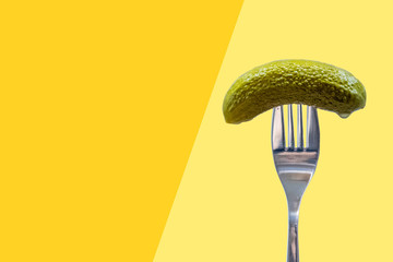 Pickle on fork, dill, gherkin, yellow and orange background, national pickle day