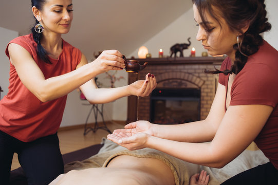 Two female masseuses doing four hands massage to young woman