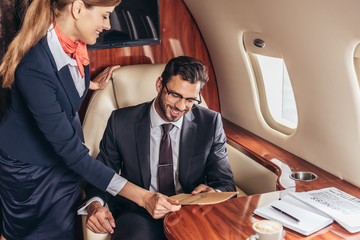 flight attendant giving menu to smiling businessman in suit in private plane