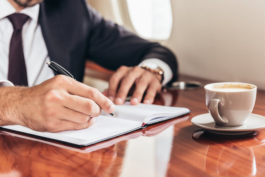 cropped view of businessman writing in notebook in private plane