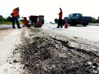 The paved road is damaged. And there are workers fixing the road