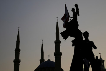 A demonstrator holds a Lebanese national flag as he sits atop a statue on Martyrs' square, as the Al-Amin mosque is seen in the background, during an anti-government protest in downtown Beirut