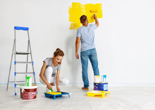 young happy couple is repairing and painting   wall at home.