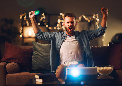 young male cheerleader watching football on tv projector at home in evening