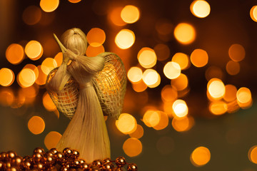 Straw angel praying on a blurred Christmas background. Beautiful bokeh created by Christmas lights. Traditional hand-made doll as a Christmas tree decoration.