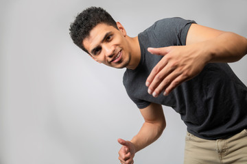 Young Hispanic man dancing and inviting to have fun- man in studio smiling