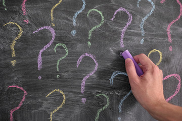 Man drawing colorful question marks on blackboard