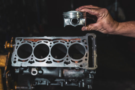 Engine cylinder in the hands of a mechanic. Car engine repair in the garage.
