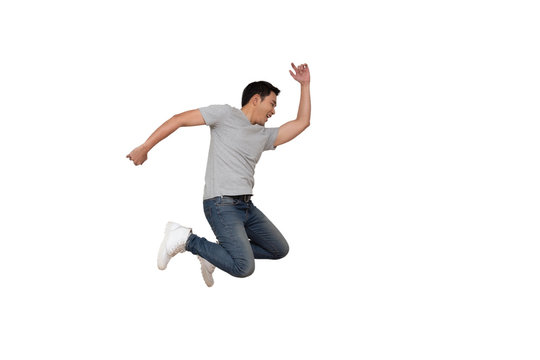 Full length portrait of an excited young Asian man in gray t-shirt jumping while celebrating success or dancing with music isolated over white background