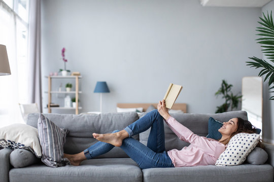 Young beautiful woman is reading a book while lying on a sofa in the living room.